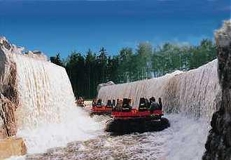 < Boote bei der Durchfahrt der beidseitigen Wasserfälle des Mountain Rafting (c) www.themeparks.de >